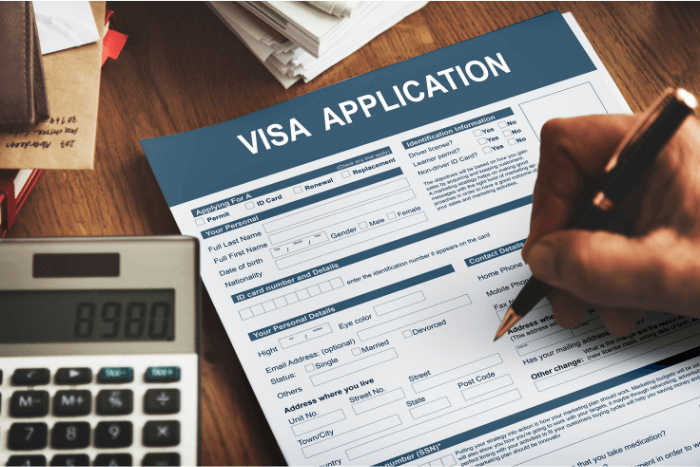 Hand filling out a visa application